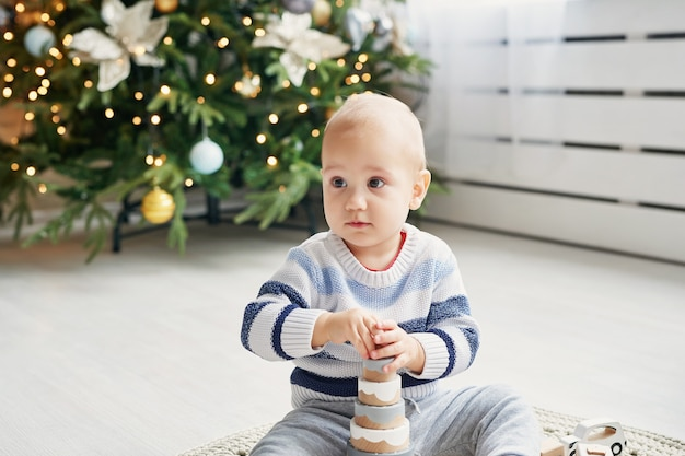 Schattige kleine jongen speelt met speelgoed houten trein, speelgoedauto, piramide en kubussen, leren ontwikkelingsconcept. ontwikkeling van fijne motoriek van kinderen, verbeelding en logisch denken
