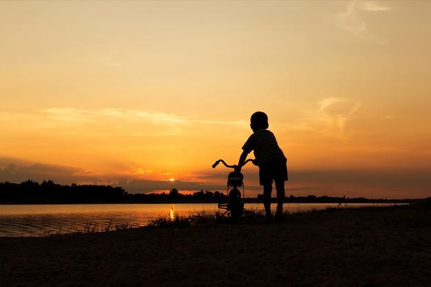 Schattige kleine jongen spelen en paardrijden fiets zonsondergang achtergrond