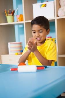 Schattige kleine jongen spelen met boetseerklei in de klas