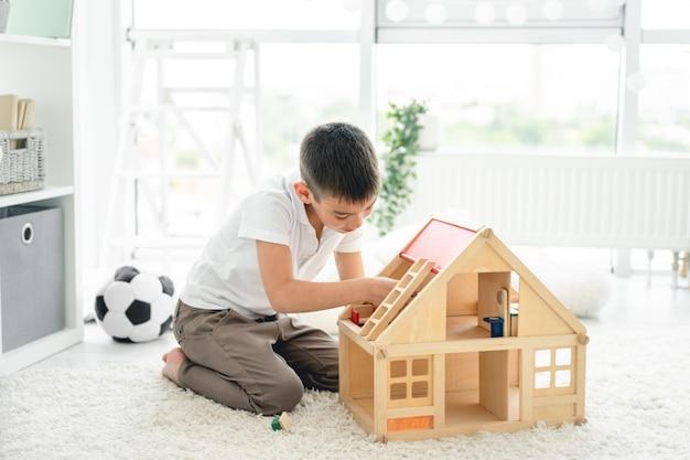 Schattige kleine jongen spelen met poppenhuis