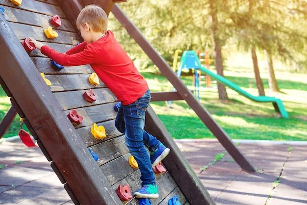 Schattige kleine jongen spelen op de speelplaats