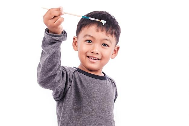 Schattige kleine jongen spelen penseel