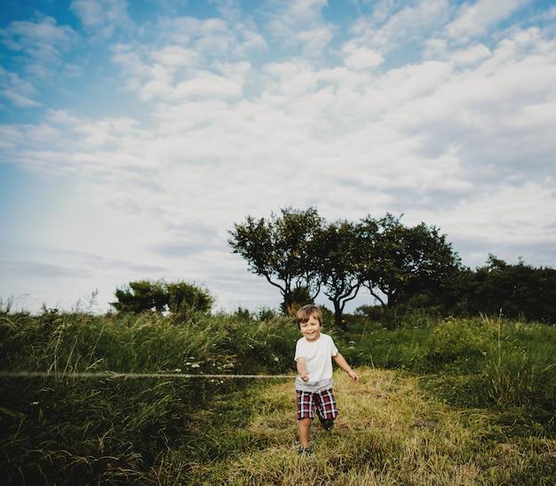 Schattige kleine jongen staat op een groen veld in de stralen van de avond
