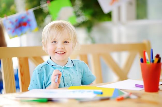 Schattige kleine jongen tekenen en schilderen met kleurrijke markeringen op de kleuterschool