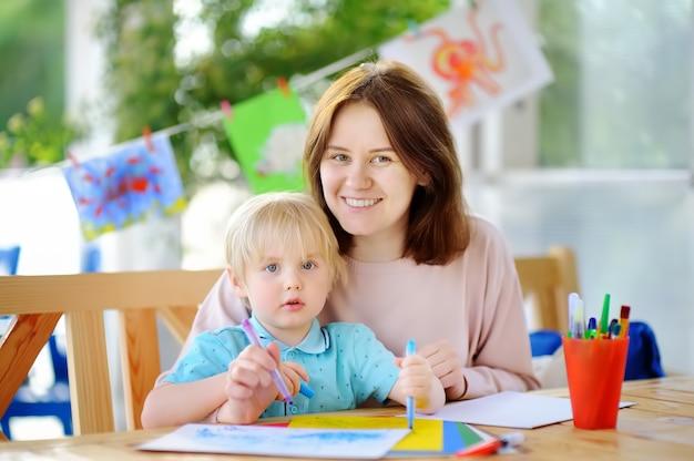 Schattige kleine jongen tekenen en schilderen met kleurrijke markeringen pennen op de kleuterschool