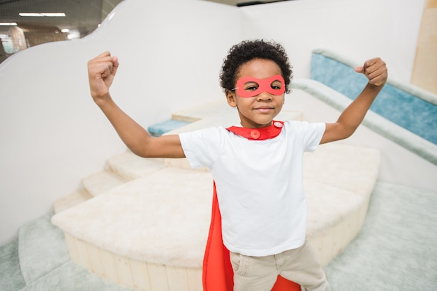 Schattige kleine jongen van afrikaanse afkomst, gekleed in een rode mantel van superheld en witte vrijetijdskleding die zijn macht toont