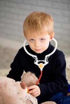 Schattige kleine jongen verkleed als arts spelen met speelgoed thuis dragen.