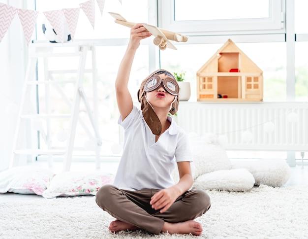 Schattige kleine jongen vliegen houten vliegtuig zittend op de vloer in de speelkamer