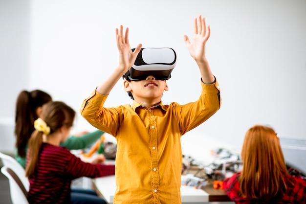Schattige kleine jongen vr virtual reality-bril in een klas robotica