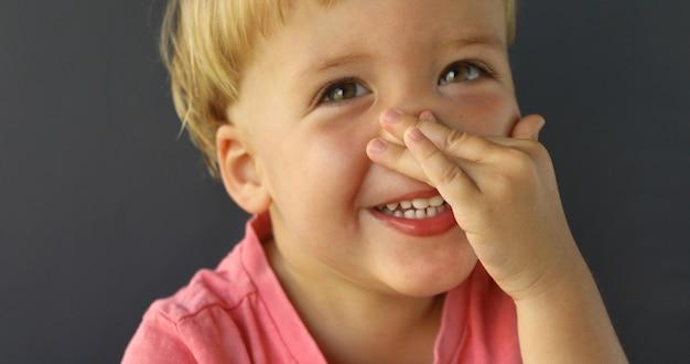 Schattige kleine jongen wijs op zijn neus