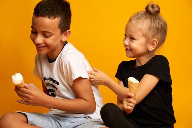 Schattige kleine jongen wil geen ijsje delen met zijn zus