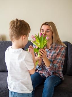 Schattige kleine jongen zijn moeder bloemen geven