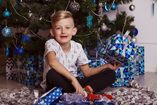 Schattige kleine jongen zit met een cadeau in de buurt van de kerstboom.