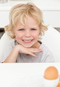 Schattige kleine jongen zittend aan een tafel om een gekookt ei te eten