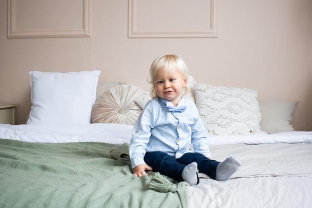 Schattige kleine jongen zittend op bed. mensen, kinderen, rust en comfortconcept.