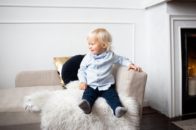 Schattige kleine jongen zittend op de bank thuis. mensen, kinderen, rust en comfortconcept.