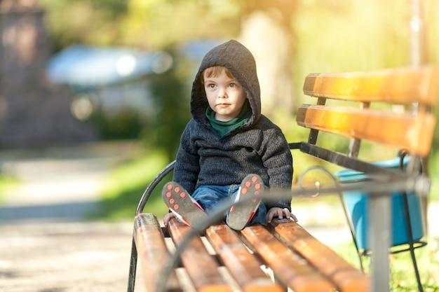 Schattige kleine jongen zittend op een bankje