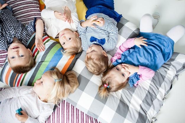 Schattige kleine jongens en meisjes liggend op de kussens en spelen in de kleuterschool, bovenaanzicht