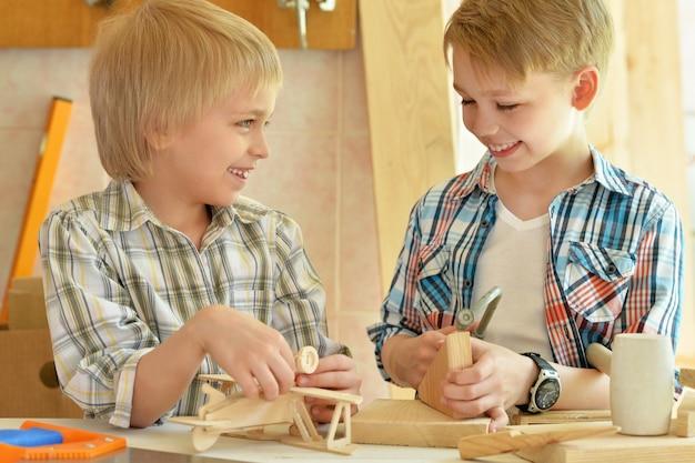 Schattige kleine jongens werken met hout in werkplaats