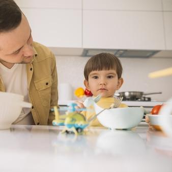 Schattige kleine kind en zijn vader in de keuken