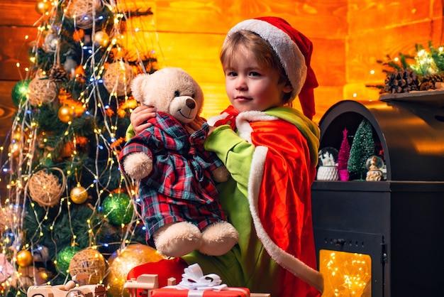 Schattige kleine kind jongen spelen in de buurt van kerstboom. geschenken en verrassingen. vrolijk kerstfeest en een gelukkig nieuwjaar. kinderen genieten van de wintervakantie thuis. huis gevuld met vreugde en liefde. familiedag kerstmis.