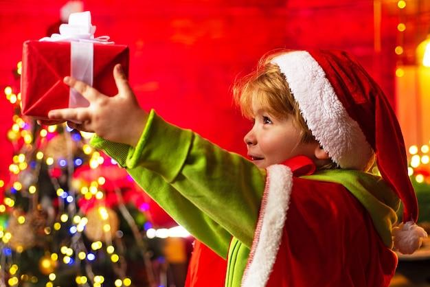 Schattige kleine kind jongen spelen in de buurt van kerstboom. Premium Foto