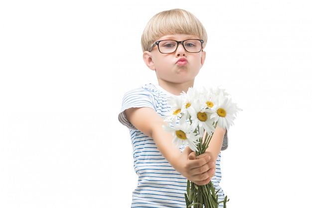 Schattige kleine kind met bloemen. jongen met kamille. schattige jongen feliciteert zijn moeder met bloemboeket. geïsoleerde jongen op een witte achtergrond.