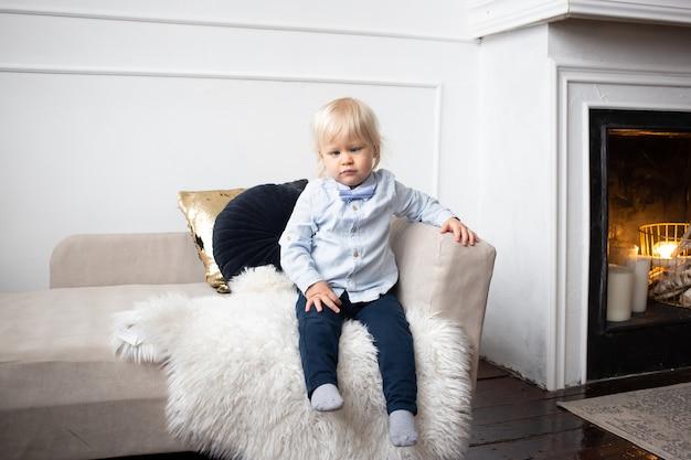 Schattige kleine kind zittend op de bank thuis. mensen, kinderen, rust en comfortconcept.