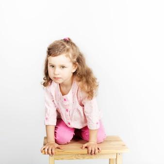 Schattige kleine kind zittend op de stoel en glimlachen