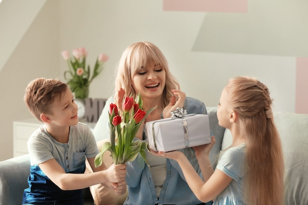 Schattige kleine kinderen feliciteren hun moeder thuis