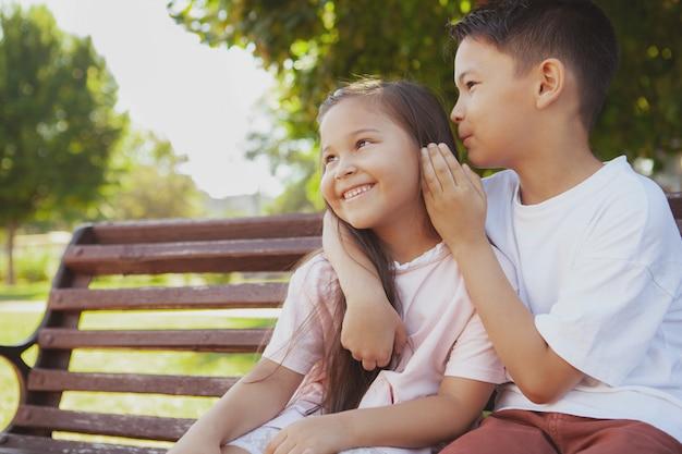 Schattige kleine kinderen genieten van warme zonnige dag in het park