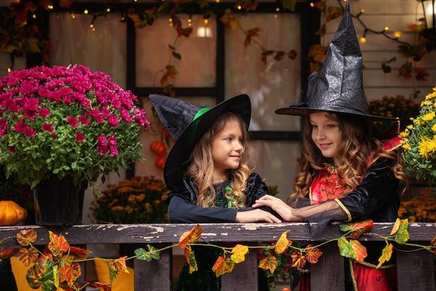 Schattige kleine kinderen meisjes met pompoen snijden gelukkige familie voorbereiden op halloween grappige kinderen a
