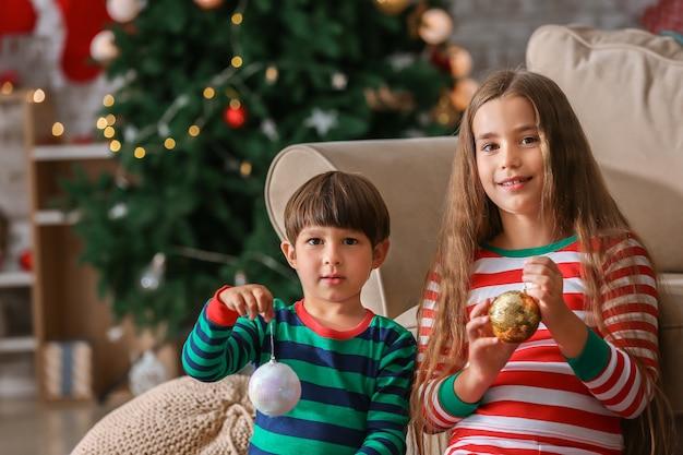 Schattige kleine kinderen met kerstballen thuis