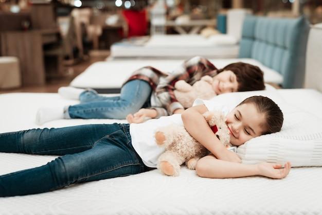 Schattige kleine kinderen slapen op matras in winkel