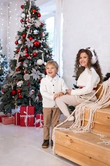 Schattige kleine kinderen spelen in de buurt van kerstboom en licht