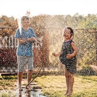 Schattige kleine kinderen spelen samen met een tuinslang op warme en zonnige zomerdag bij zonsondergang