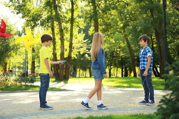 Schattige kleine kinderen springtouw in park