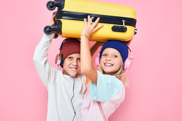 Schattige kleine kinderen stijlvolle kleding koffer hoofdtelefoon geïsoleerde achtergrond