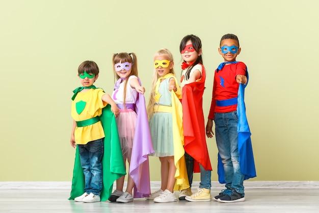 Schattige kleine kinderen verkleed als superhelden in de buurt van kleurenmuur