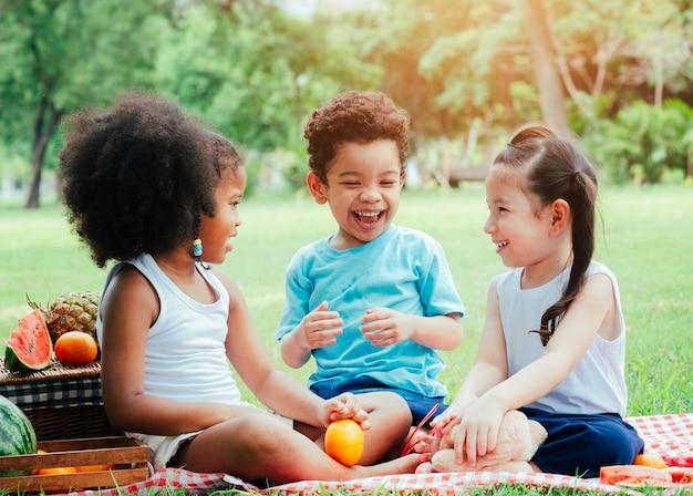 Schattige kleine kinderen verschillende etnische spelen in het park op zomerdag