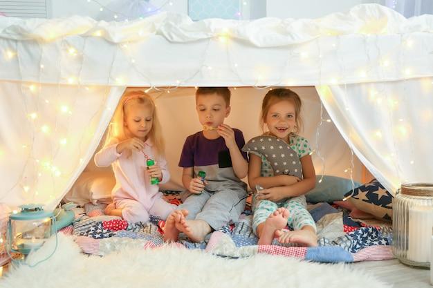 Schattige kleine kinderen zeepbellen blazen in krot thuis at