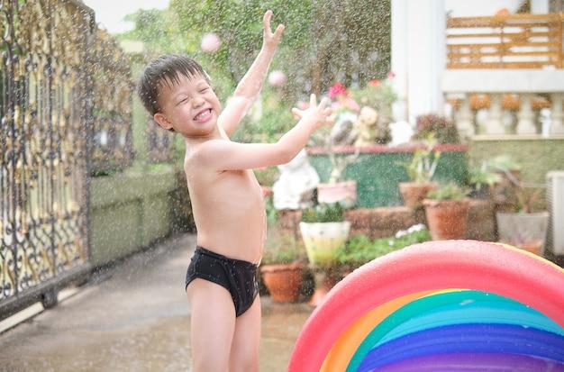 Schattige kleine lachende azië peuter jongenskind plezier spelen met plons water in de tuin thuis in de zonnige ochtend