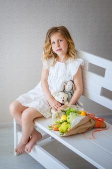 Schattige kleine meid droomt ervan om een prinses te worden. lichte kinderkamer met een wit interieur, bloemen en speelgoed