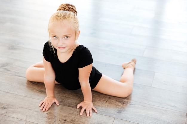 Schattige kleine meisje ballerina die zich uitstrekt op de vloer in dansstudio