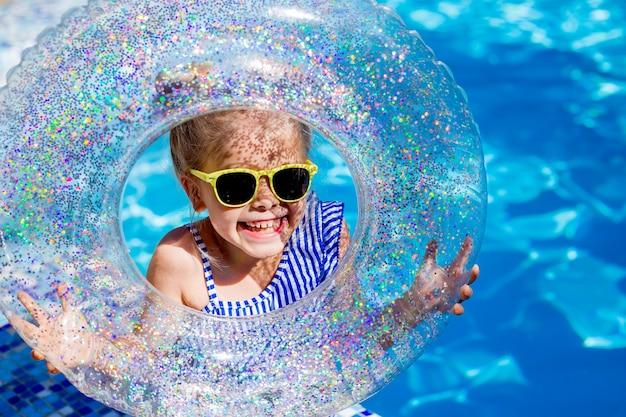 Schattige kleine meisje blonde in zonnebril lacht in het zwembad met een reddingslijn