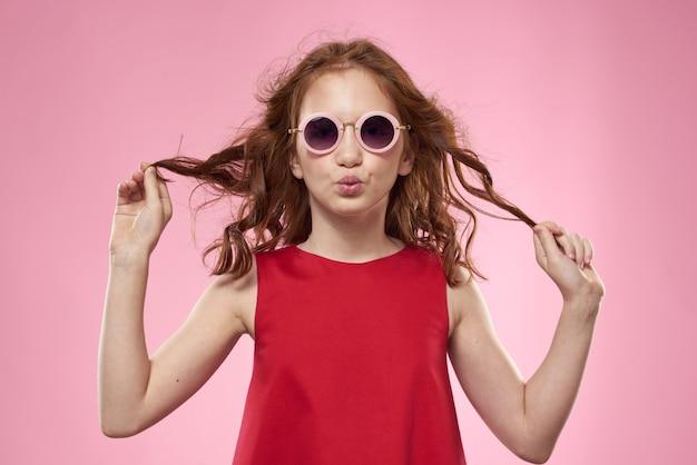 Schattige kleine meisje rode jurk zonnebril studio roze achtergrond