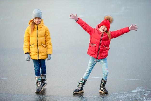 Schattige kleine meisjes die op de ijsbaan schaatsen