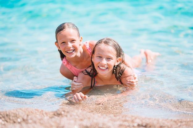 Schattige kleine meisjes die plezier hebben op het strand
