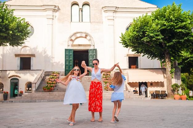 Schattige kleine meisjes en jonge moeder hebben plezier in het italiaanse oude dorp