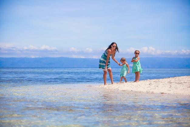 Schattige kleine meisjes en jonge moeder hebben plezier op tropisch wit strand in onbewoond eiland
